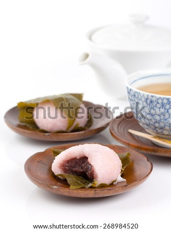 Sakuramochi is a type of traditional Japanese confectionery (wagashi) made of sweet pink-colored rice cake stuffed with red bean paste (anko), wrapped in a pickled cherry leaf.  - stock photo