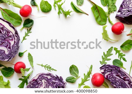 Salad baby leaves, radishes and cabbage background with blank space in the center, salad concept - stock photo