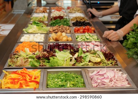Salad bar with various fresh vegetables and other foods - stock photo