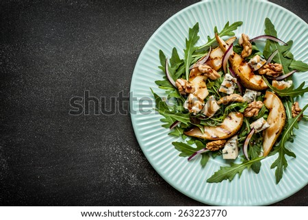 Salad - blue cheese, pear, arugula, walnuts, red onion and balsamic vinegar dressing on pastel blue plate from above. Black chalkboard as background. Layout with free text space. - stock photo