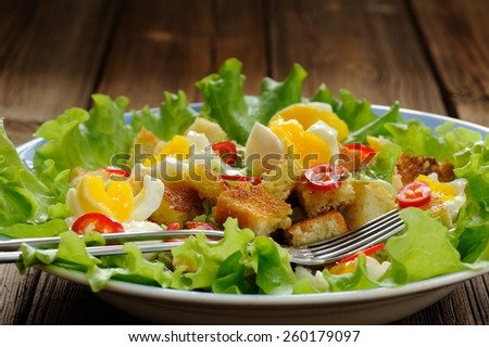 Salad Caesar with eggs, chili pepper and two forks closeup
