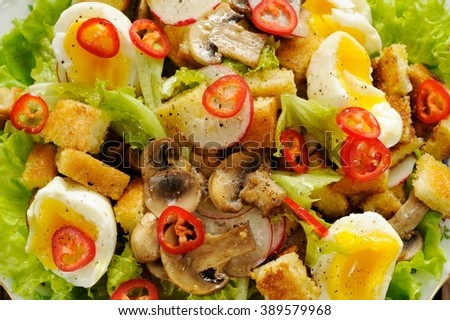 Salad Caesar with mushrooms, eggs, chili and radish with two forks on wooden background closeup horizontal - stock photo