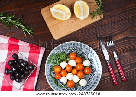 Salad caprese made with arugula, tomatoes, cheese mozzarella balls and on plate with fork and knife, on  wooden table with olives, lemon and rosemary - stock photo