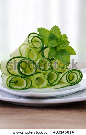 Salad cucumber ribbons twisted in rolls with mint - stock photo