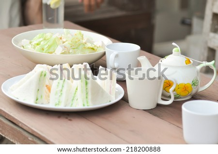 salad dish, sandwich dish  and some tea on the table - stock photo