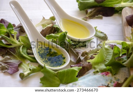 Salad dressing of olive oil, vinegar and parsley with salad leaves - stock photo