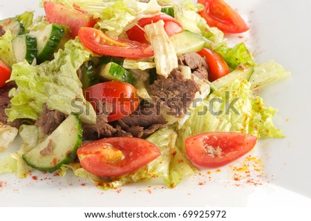 Salad from beef, tomatoes, cucumbers with sauce from olive oil of balsam vinegar on a light plate. A shot horizontal, focus in the center a shot. - stock photo