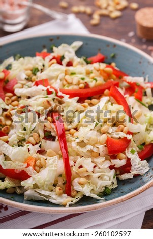 Salad from cabbage with red pepper and pine nuts..selective focus