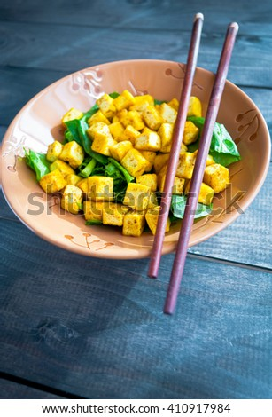 Salad from fried tofu with curry and fresh spinach served in brown bowl with chopsticks on wooden background - stock photo