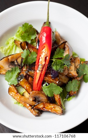 Salad from roasted eggplants, mushrooms, soy sauce, oyster sauce, cilantro and garlic - stock photo
