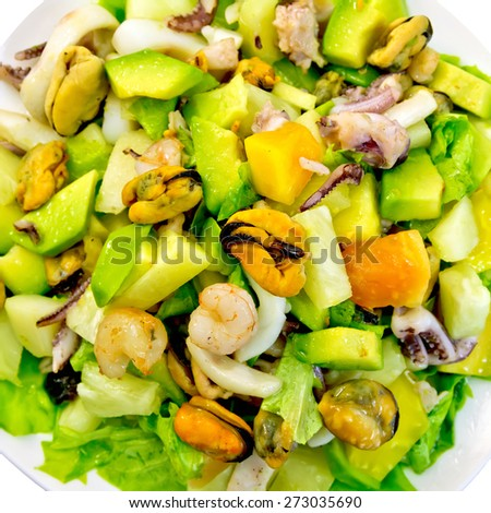 Salad from shrimps, octopus, mussels and calamari with avocado, lettuce, pineapple isolated on white background top - stock photo