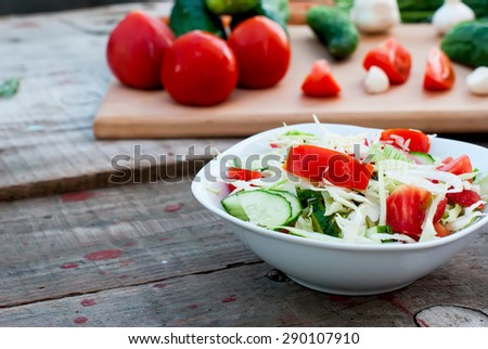 salad in a bowl of tomato, cucumber, cabbage vegetables for salad in the background, selective focus - stock photo