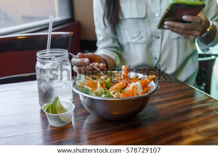 Salad in a bowl with glass of water in a wood table.