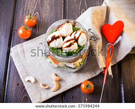 Salad in mason jars with tomatoes, leaves, mozzarella on wooden table. A red heart. - stock photo