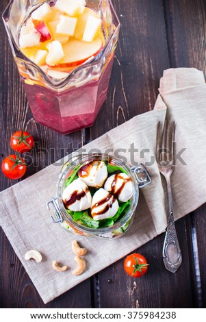 Salad in mason jars with tomatoes, leaves, mozzarella on wooden table with a pitcher of fruit juice. A red heart. - stock photo