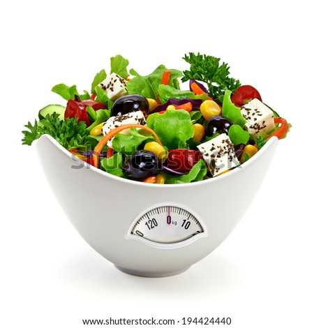 Salad in porcelain bowl with weight scale on white background