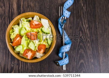 Salad in wooden bowl and measuring tape on a dark table close-up. Concept of healthy nutrition and diet.