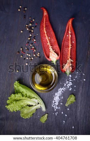 Salad ingredients: red pepper, lettuce, olive oil on rustic wooden background. Fresh vegetables, top view. - stock photo