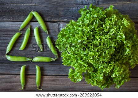 Salad lettuce and green peas healthy organic nutrition food on vintage wooden background. Rustic style and natural light. - stock photo