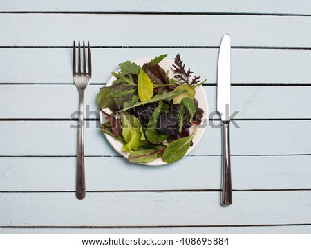 Salad mix in plate on wooden table. Salad with spinach, arugula, romaine and lettuce on white platter with fork and knife, top view. Diet and weight loss concept. - stock photo