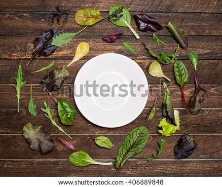 Salad mix laid out around a white plate saucer with place for text, salad leaves frame on wooden rustic background top view. - stock photo