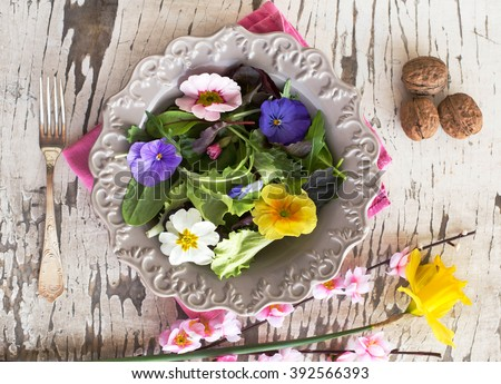 salad mix with edible flowers in rustic background