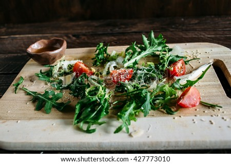 Salad of arugula, arugula and tomato, arugula salad with tomatoes and parmesan, salad on a wooden board, salad on a brown background, salad with sesame seeds - stock photo