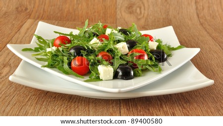 Salad of arugula with cherry tomatoes, slices of cheese and grapes