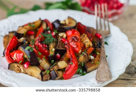 Salad of baked vegetables. Eggplant and bell peppers with pomegranate - stock photo
