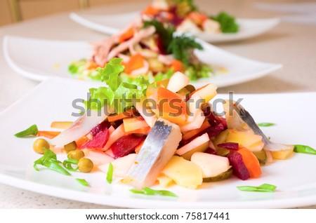 salad of beetroot, carrot, potato, green leek and herring - stock photo