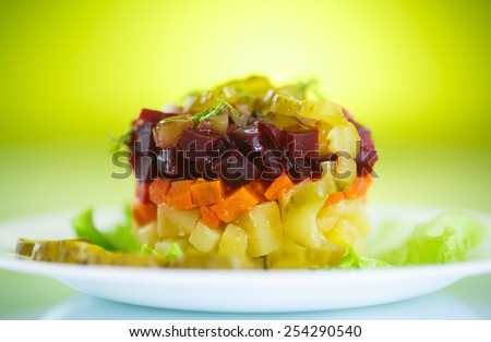 salad of boiled vegetables with beets on a green background - stock photo