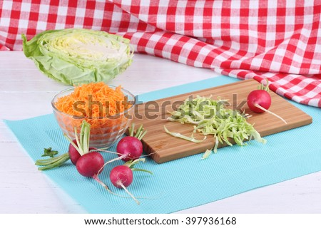 Salad of cabbage, carrot and radish cooking at the kitchen. Diet food with lot of vitamins for healthy and energy. - stock photo