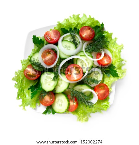Salad of cucumbers, tomatoes and greens on a white background, top view - stock photo