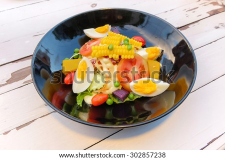 Salad of egg,corn, tomatoes, cucumbers, olives on a plate. - stock photo