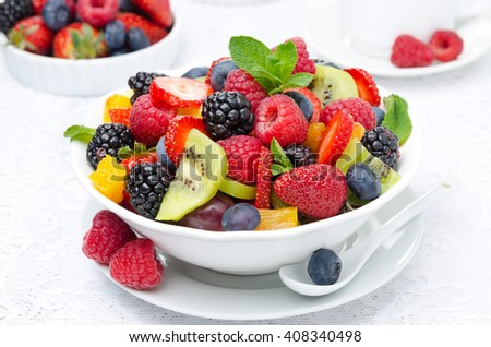 salad of fresh fruit and berries in a white bowl, berries and cup of tea in the background, closeup - stock photo