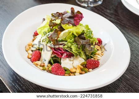 Salad of fresh greens, gorgonzola cheese, pine nuts, raspberries - stock photo