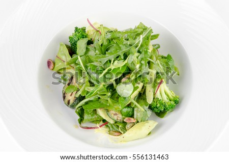 Salad of green vegetables with broccoli, zucchini and walnut dressing on a plate on a white background, closeup