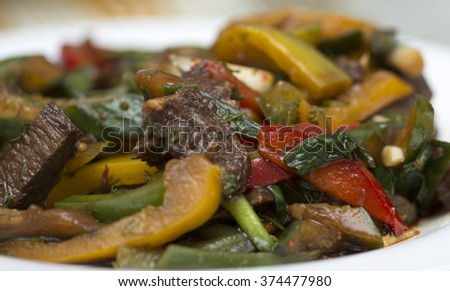 salad of meat, sweet pepper, cucumber on a white plate