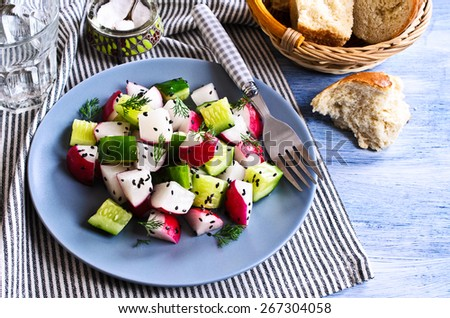 Salad of radish and cucumber with sesame seeds and dill