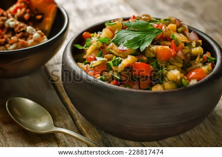 salad of roasted eggplant and peppers on a dark wood background. tinting. selective focus on parsley