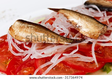 Salad of sardine with fresh cut tomatoes and white onion.