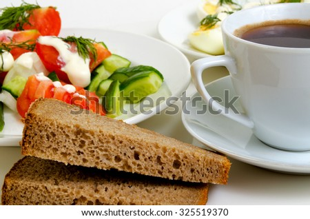 Salad of tomatoes and cucumbers, eggs, bread and coffee. - stock photo