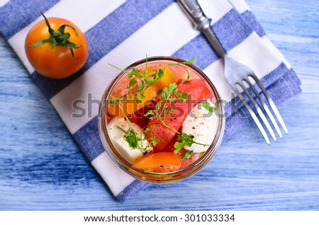 Salad of tomatoes and mozzarella with watercress in a glass container. Selective focus. - stock photo