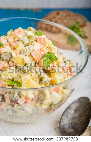 Salad olivier in bowl on blue table. Russian traditional salad. - stock photo