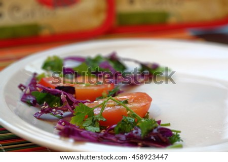 Salad on the corner of the white plate.