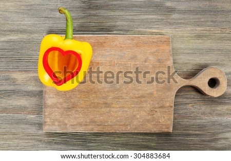 Salad pepper with cut in shape of heart on wooden background - stock photo
