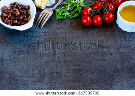 Salad preparation ingredients (olive oil, herbs leaves, tomatoes, garlic and olives) on dark vintage background with space for text. - stock photo