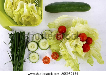 Salad preparation with cucumbers, lettuce, cherry tomatoes and chives on modern white wood table setting, overhead. - stock photo