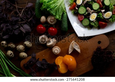 salad preparation with quail eggs, mushrooms, mix red yellow and cherry tomatoes, cucumber, basil, brie cheese, lettuce, and black olives organic fresh from farmers market rustic  dark wood background - stock photo