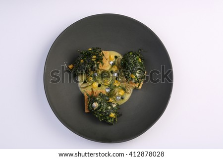 Salad seaweed, fish, croutons, corn and souse on black plate - stock photo
